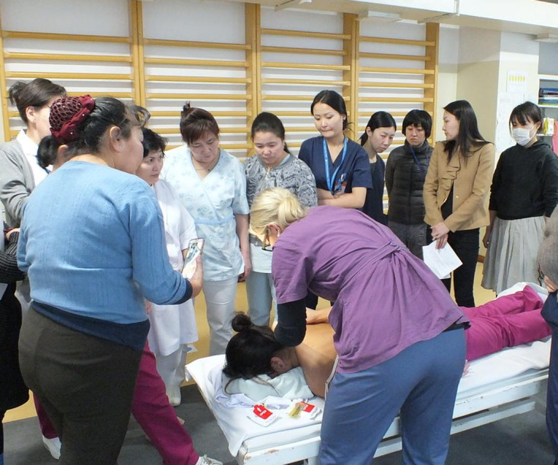 A professional physical therapist volunteering in Mongolia runs a workshop for local medical staff.